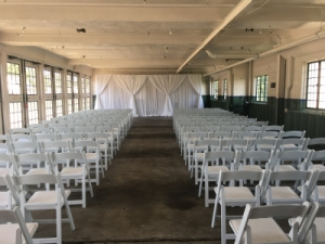 wedding ceremony set up with white folding chairs in the Packard Lodge Garage building