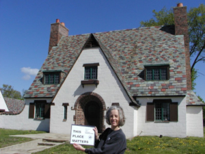 photo of the lodge building after some restoration work had been done, and Hilary Davis is standing in front with a proud smile at the Packard Proving Grounds Historic Site